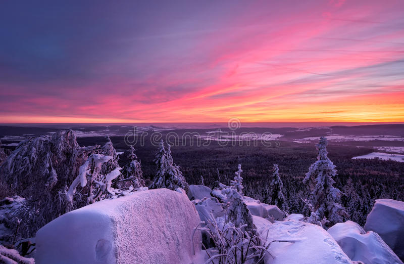 Tramonto vibrante nell'inverno con gli alberi e le rocce innevati, Baviera, Germania immagini stock