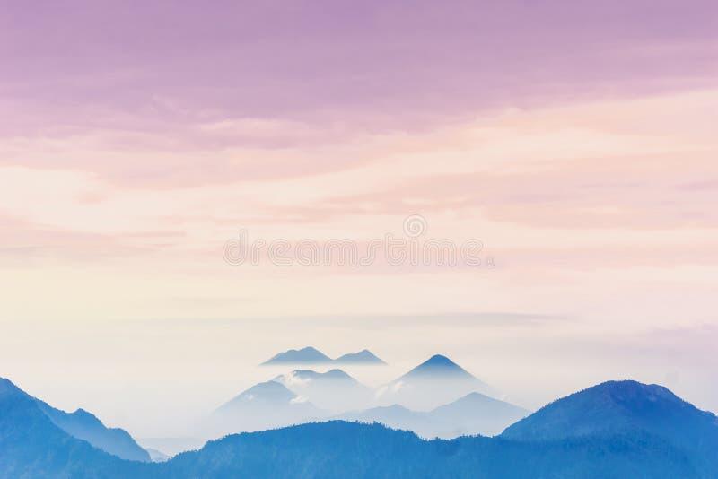 Tramonto viola sopra i vulcani nebbiosi di Lago Atilan da Quetzaltenango nel Guatemala fotografia stock