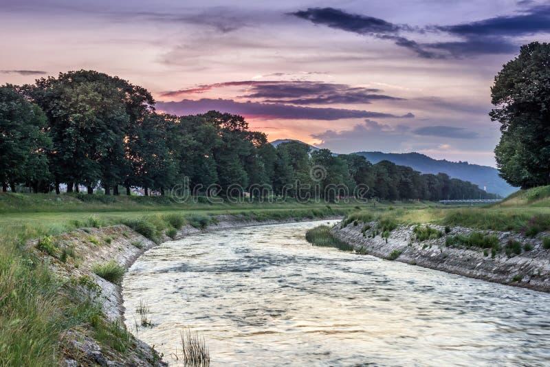 Tramonto vivo sopra un fiume con le riflessioni dell'acqua immagini stock