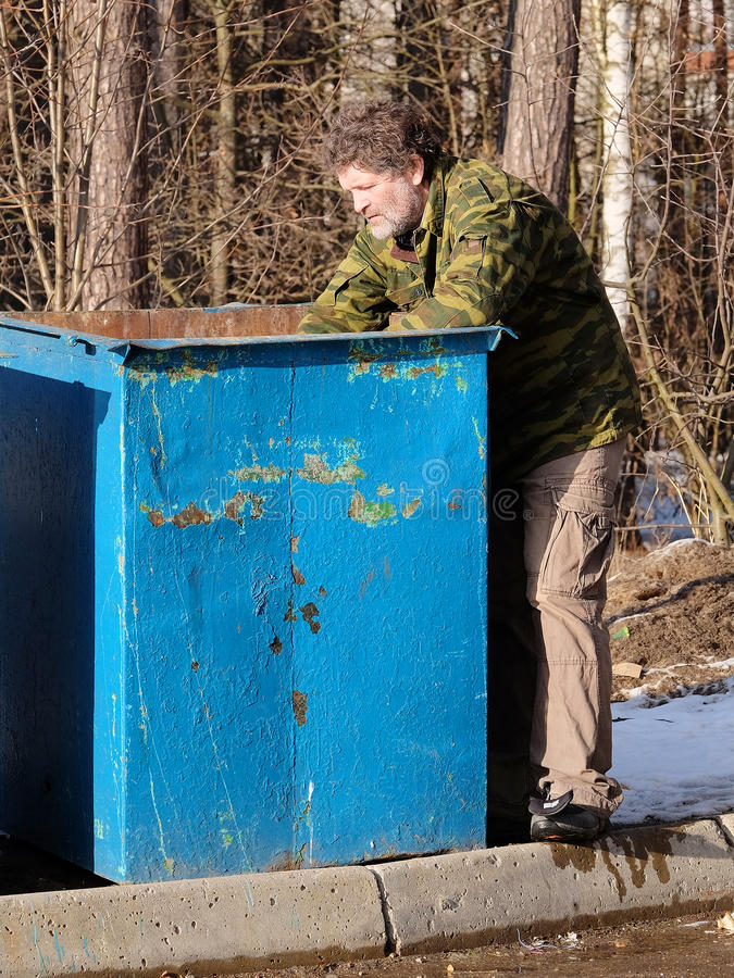Tramp near the garbage bin. The image of tramp near the garbage bin stock photo