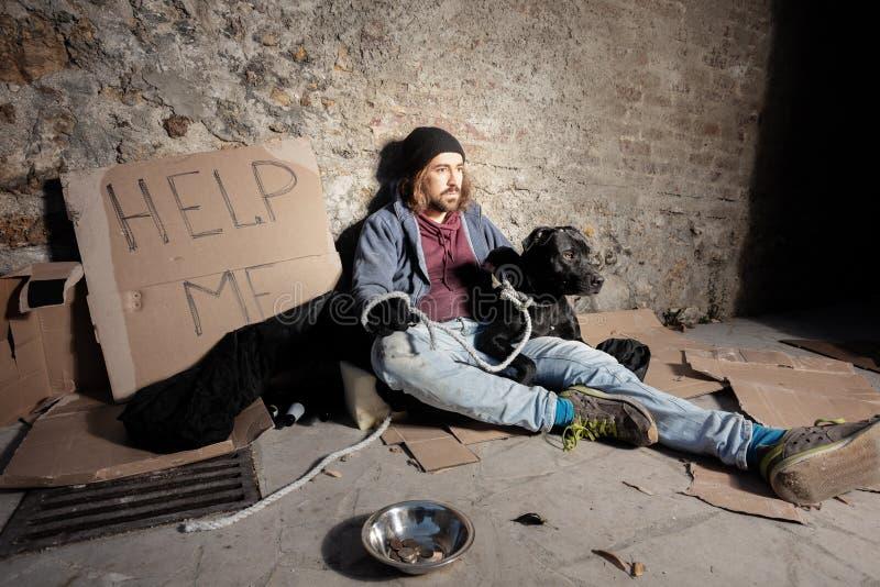 Trampeln Sie, seinen Hund umarmend, der auf dem Stadtbürgersteig sitzt stockfoto