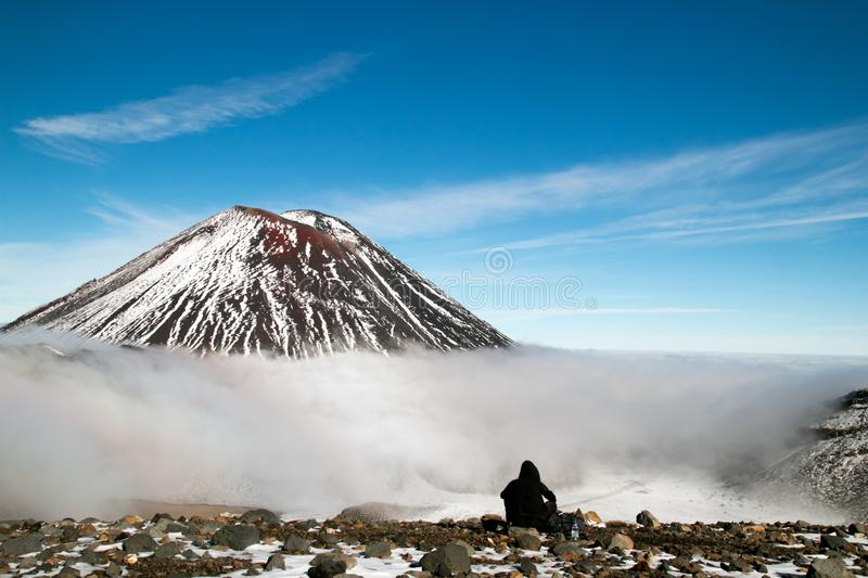 Tramper having rest in front of active volcano, mountain hiker and climber having snack and enjoys spectacular view of Mt Ngauruho stock photography