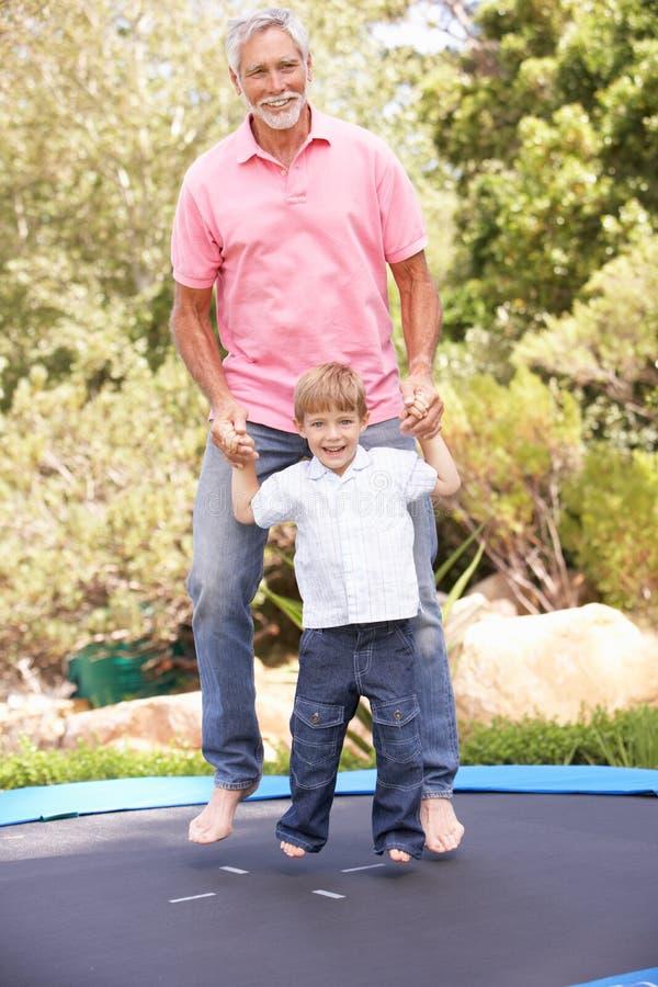 trampoline för farfarsonsonbanhoppning royaltyfri foto