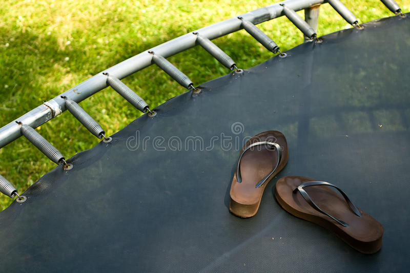 Trampoline with Flipflops. Trampoline with a pair of brown flipflops stock photo