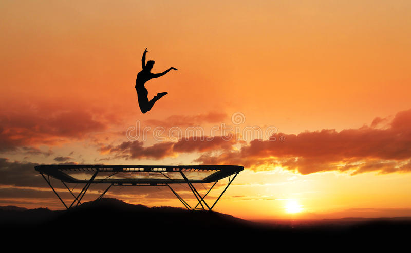 Trampoline gymnast. Silhouette of female gymnast on trampoline in sunset stock photos
