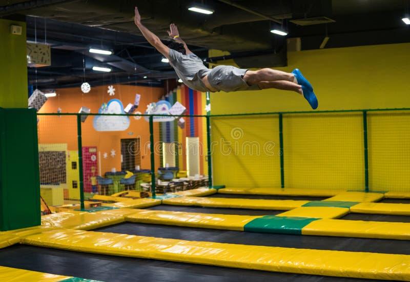 Trampolinepullover führt akrobatische Übungen auf der Trampoline durch lizenzfreies stockbild