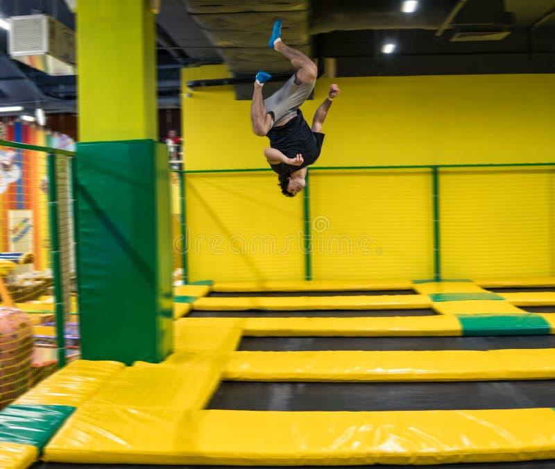 Trampolinepullover führt akrobatische Übungen auf der Trampoline durch stockfotos