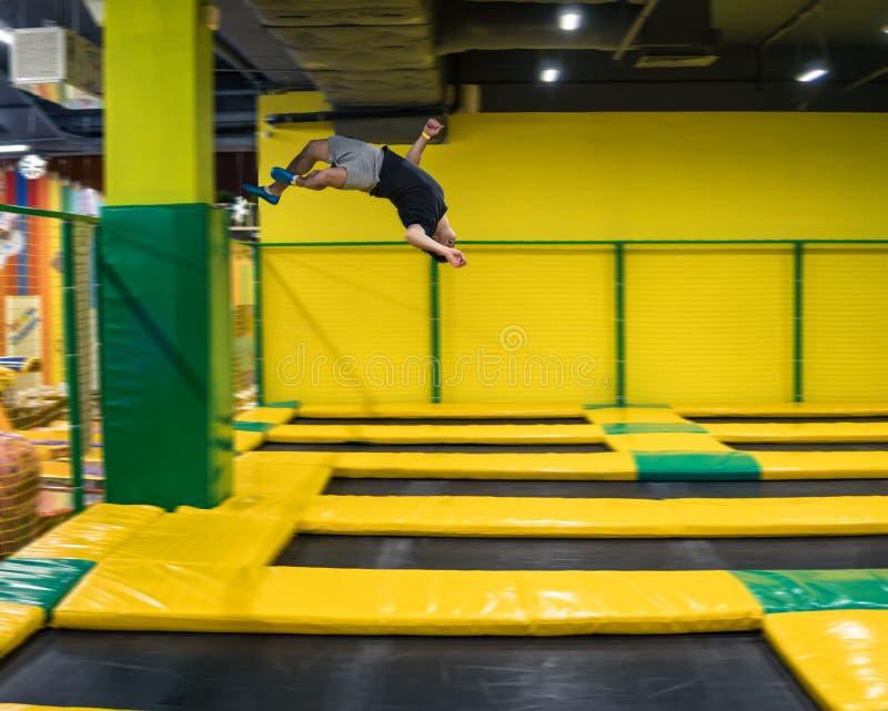Trampolinepullover führt akrobatische Übungen auf der Trampoline durch stockfotografie