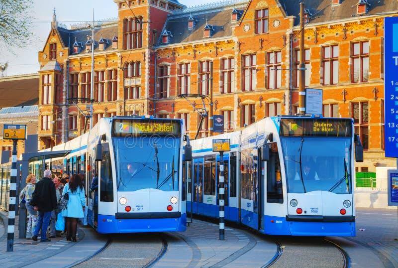 Trams bij het station van Amsterdam Centraal in Amsterdam, Ne stock fotografie