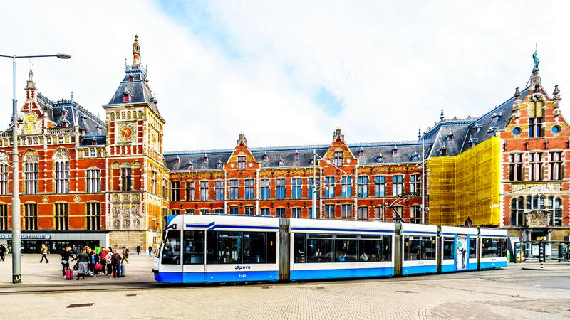 Trams coming and going at the historic Centraal Station building of the main train station in the center of Amsterdam stock photo