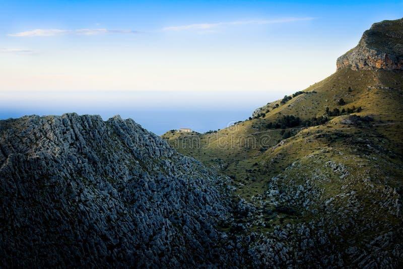 Tramuntana κοντά σε Sa Calobra, απομονωμένο σπίτι στα βουνά στο ηλιοβασίλεμα, βράχοι, πράσινα λιβάδια, Μεσόγειος, μπλε ουρανός, Μ στοκ εικόνες