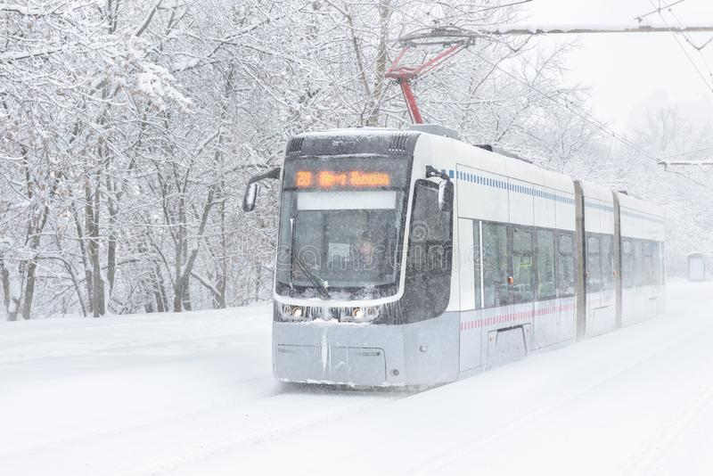 Tramwaj iść wzdłuż ulicy podczas śnieżycy przy zimą w Moskwa obraz royalty free