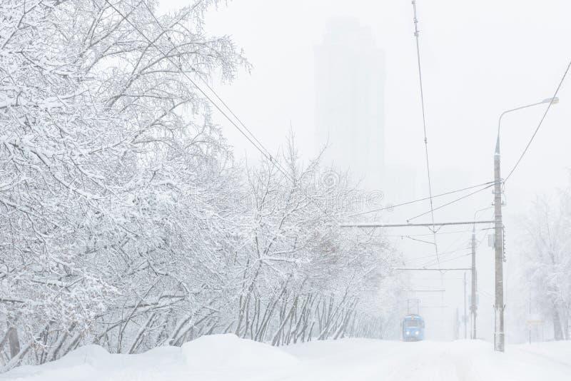 Tramwaj iść wzdłuż ulicy podczas śnieżycy przy zimą w Moskwa zdjęcia stock