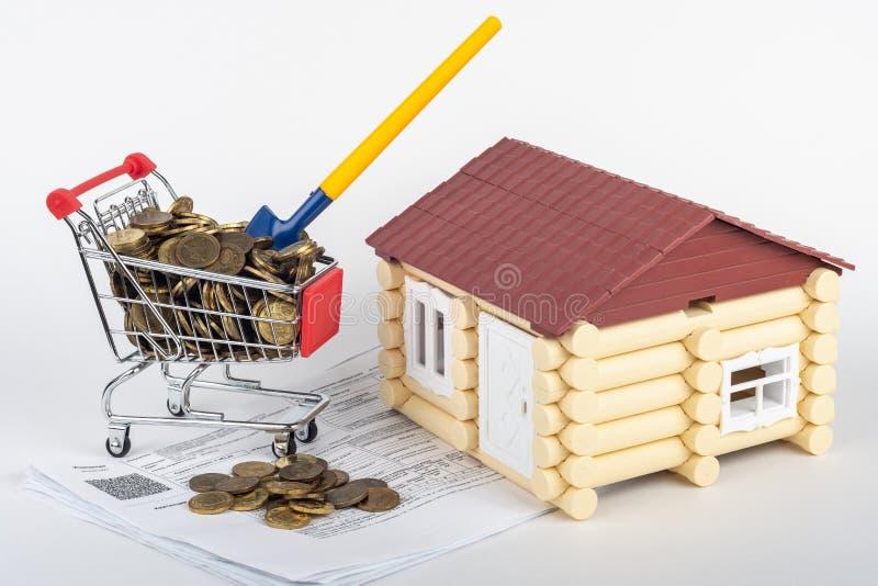 Tramwaj z pieniądze w rachunkach dla mieszkania, łopata wtykał w tramwaju, bawi się dom obok go fotografia stock