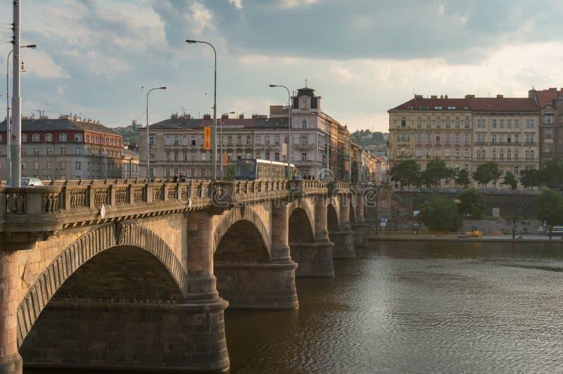 Tramwajarski poruszający na starym moście nad Vltava rzeką w Praga obrazy royalty free