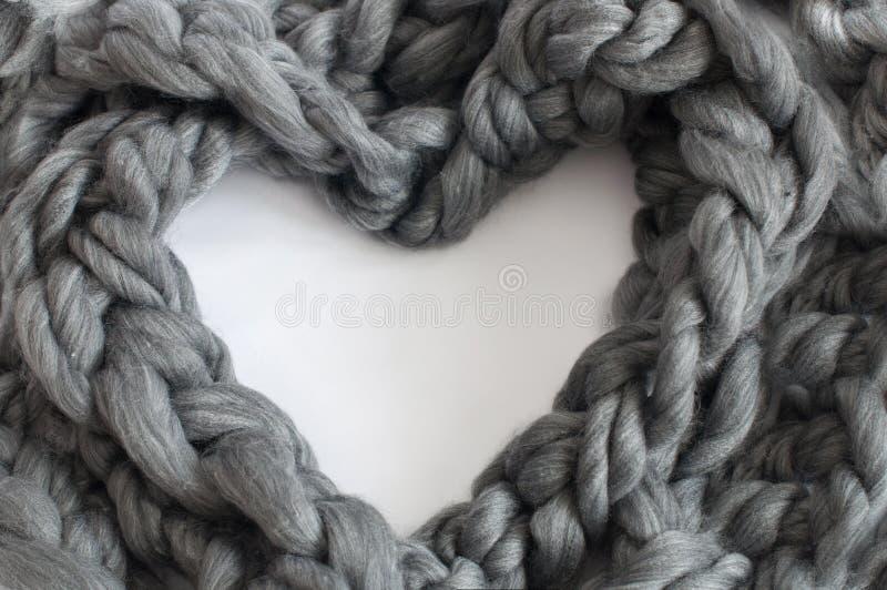 Trança de lã cinzenta em uma forma do coração fotos de stock