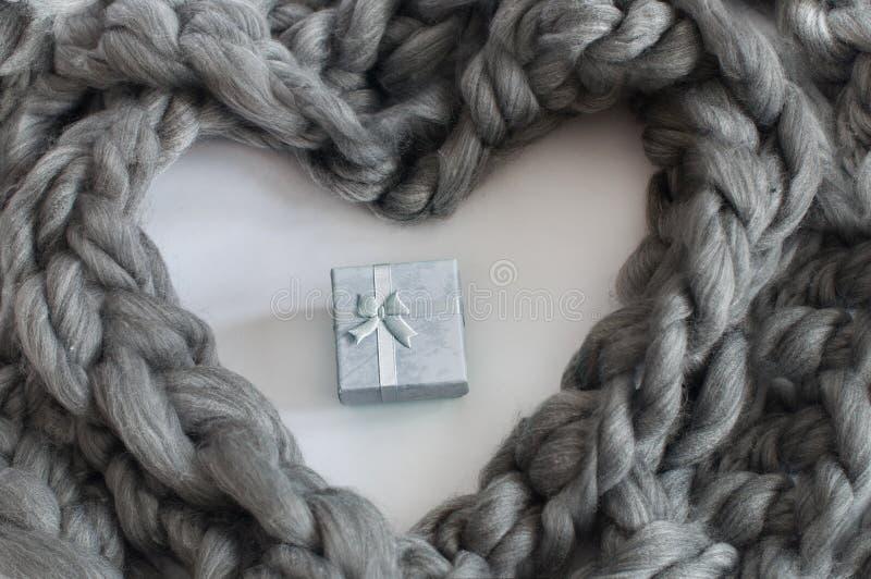 Trança de lã cinzenta em uma forma do coração com pouca caixa de presente no centro fotos de stock royalty free