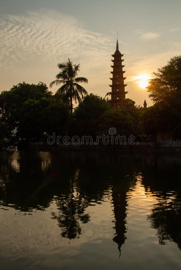 Tran Quoc Pagoda reflecting in lake, Hanoi, Vietnam at sunset. The iconic Tran Quoc Pagoda, Hanoi, Vietnam silhouetted against a pale golden sky at sunset stock photo