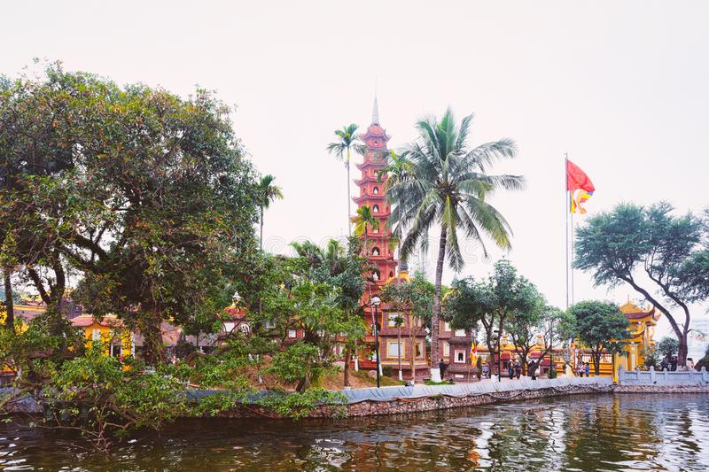 Tran Quoc pagoda on West Lake in Hanoi. Tran Quoc pagoda and vietnamese flag on West Lake in Hanoi, capital of Vietnam in Southeast Asia. Traditional tower stock photography