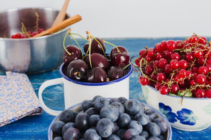 Tranbärkörsbär och vinbär i den vita bunken på åldrig träbakgrund av blått färgar royaltyfri foto