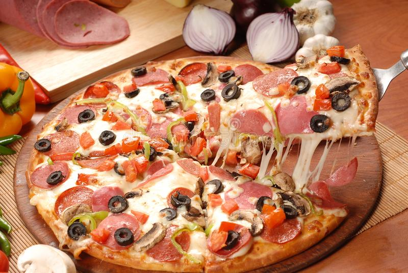 Tranche chaude de pizza avec du fromage de fonte sur une table en bois rustique images stock