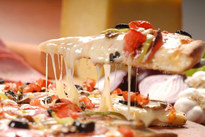 Tranche chaude de pizza avec du fromage de fonte sur une table en bois rustique image libre de droits