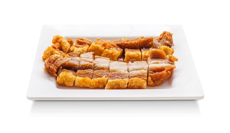 Tranche croustillante de porc sur le plat d'isolement sur le fond blanc image libre de droits