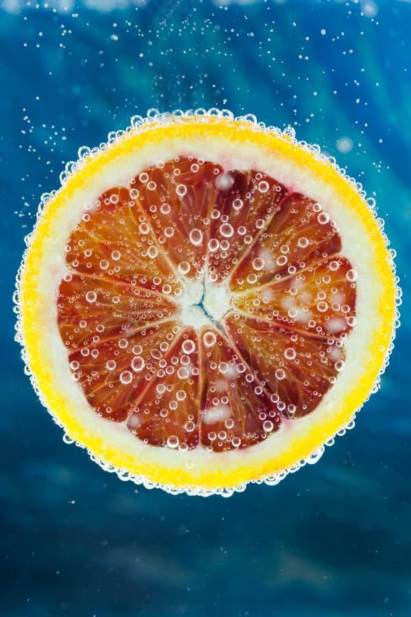 Tranche d'orange sanguine tombant dans l'eau photo stock