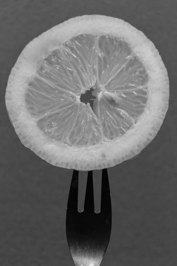 Tranche de citron piqu?e sur la fourchette images stock