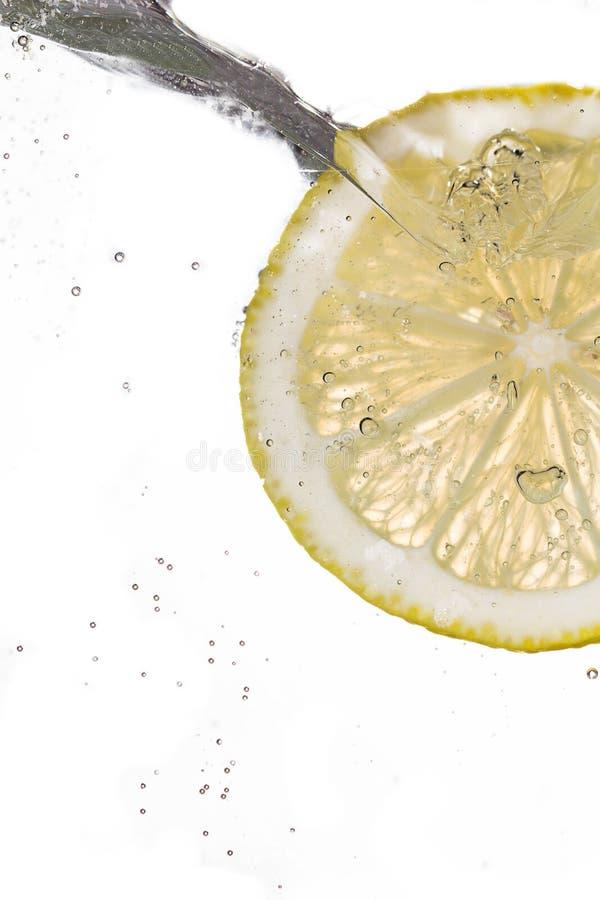 Tranche de citron tombant dans l'eau photographie stock libre de droits
