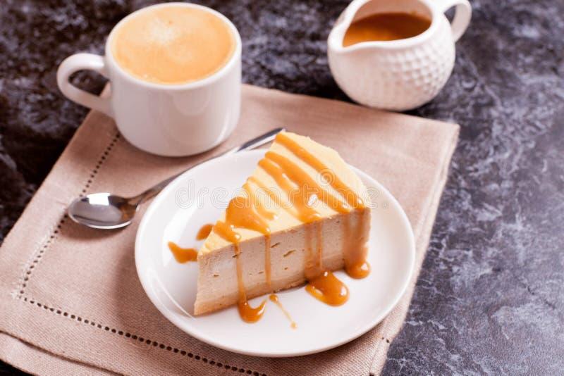 Tranche de gâteau au fromage avec de la sauce à caramel, tasse de café photographie stock libre de droits
