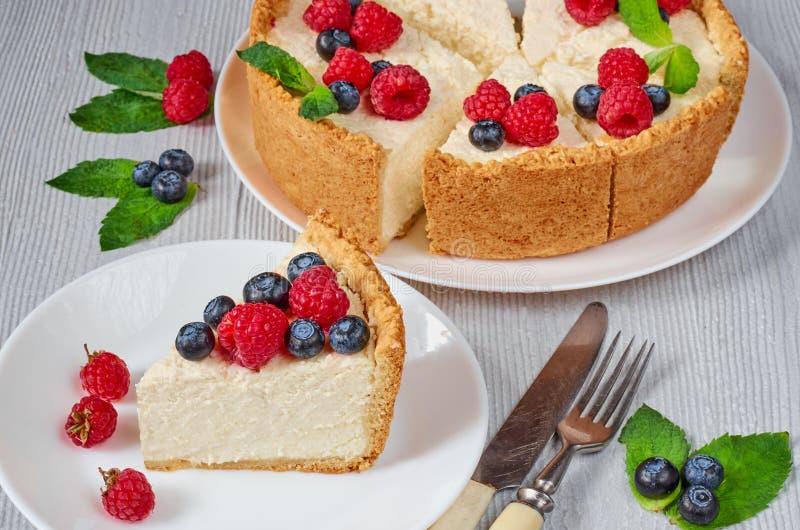 Tranche de gâteau au fromage avec les baies fraîches du plat blanc - dessert organique sain d'été Gâteau au fromage classique de  photo stock