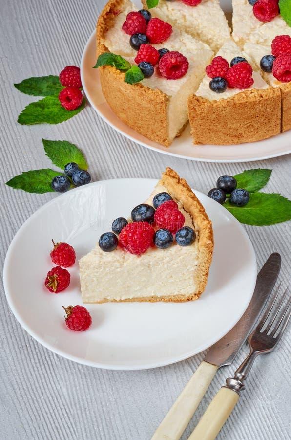 Tranche de gâteau au fromage avec les baies fraîches sur de plat de fin le dessert organique sain blanc - Gâteau au fromage class image stock