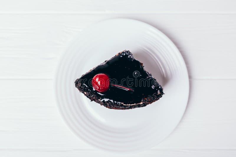 Tranche de gâteau de chocolat avec le glaçage et la cerise image stock