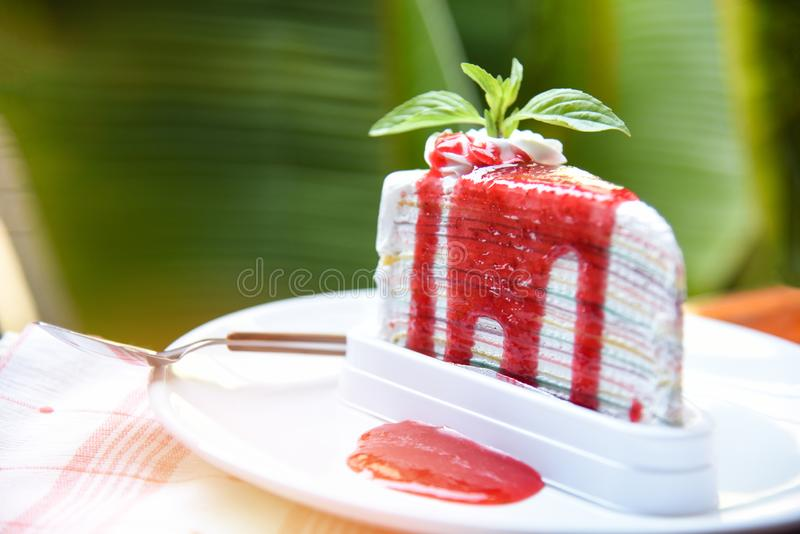 Tranche de gâteau de crêpe avec de la sauce à fraise du plat blanc - morceau d'arcs-en-ciel de gâteau avec la crème fouettée image stock