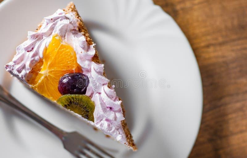 Tranche de gâteau d'anniversaire posé avec de la crème avec le fruit dans un plat sur en bois photographie stock