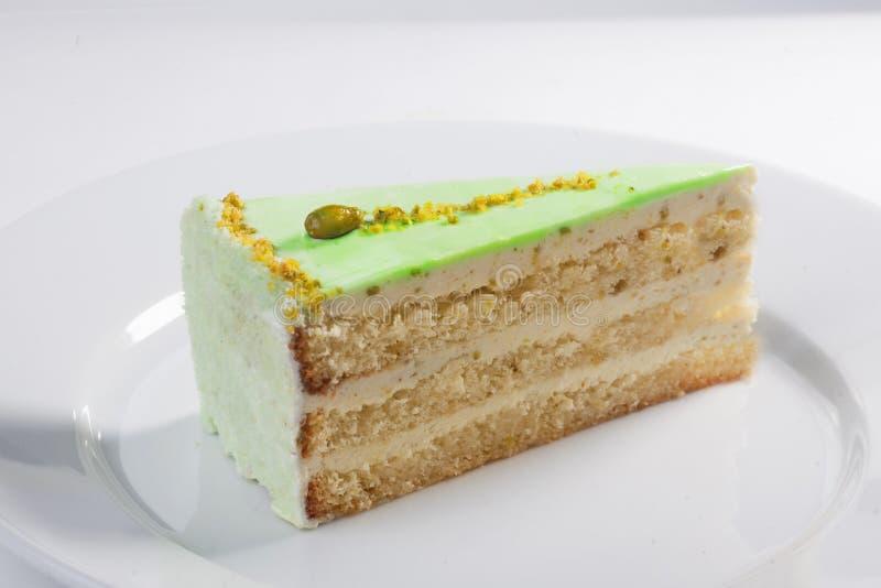 Tranche de gâteau de pistache sur un fond blanc en gros plan de plat image libre de droits