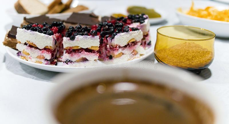 Tranche de gâteau de fruit avec la myrtille et la groseille, café dans le premier plan photos libres de droits