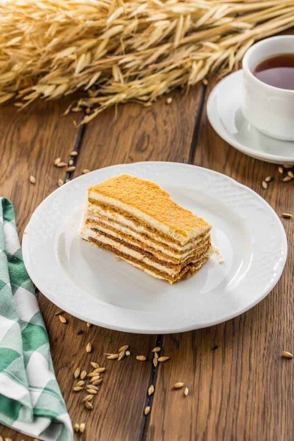 Tranche de gâteau de miel posé avec la tasse de thé sur la table en bois photo libre de droits