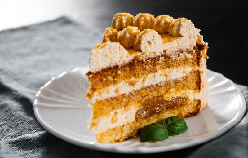 Tranche de gâteau de miel posé dans un plat images libres de droits