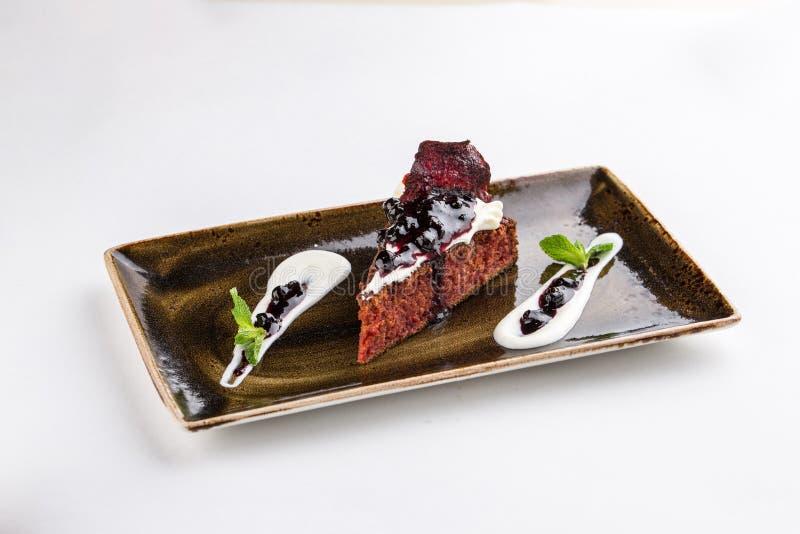 Tranche de gâteau mousseline de myrtille du plat carré brun d'isolement sur le fond blanc image stock