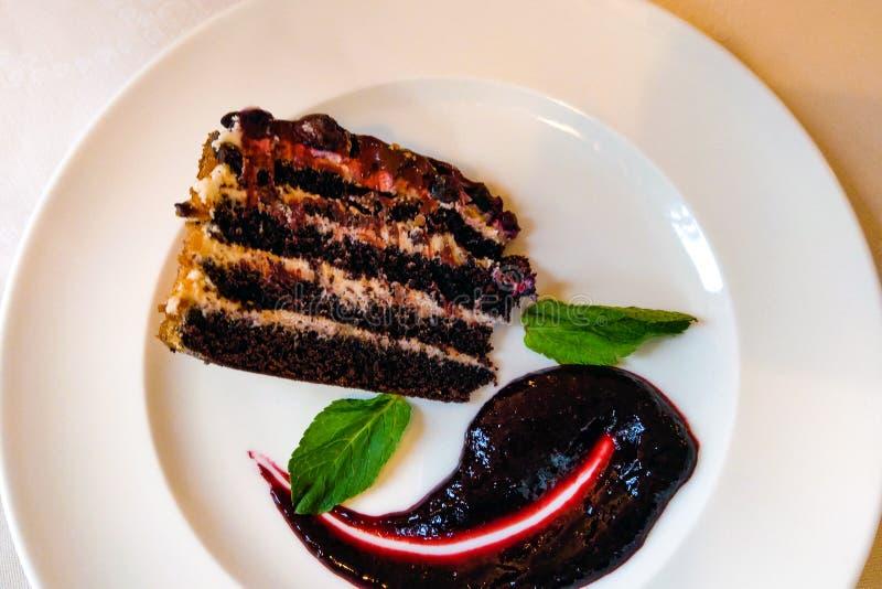 Tranche de gâteau de myrtille avec les feuilles en bon état d'un plat blanc photographie stock libre de droits