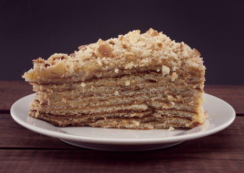 Tranche de gâteau posé avec l'écrou du plat, sur la table en bois photographie stock