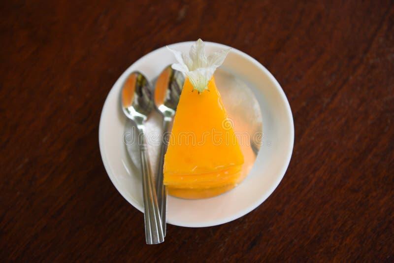 Tranche de gâteau sur le palte blanc avec la fleur et la cuillère sur le fond en bois de table - gâteau orange délicieux photos libres de droits