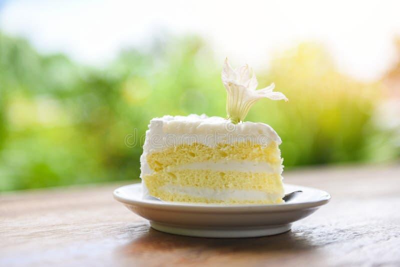 Tranche de gâteau sur le palte blanc avec la fleur sur le fond en bois de nature de table - gâteau de noix de coco délicieux image stock