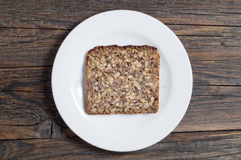 Tranche de pain avec des graines dans un plat photographie stock