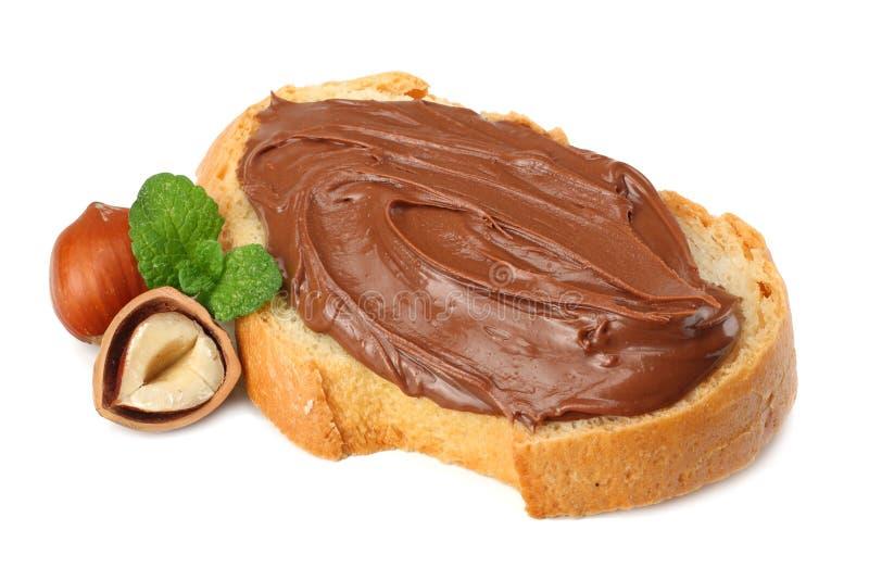 Tranche de pain avec de la crème de chocolat avec la noisette d'isolement sur le fond blanc images stock