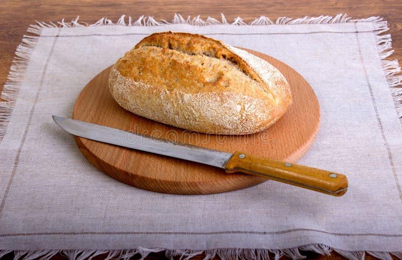 Tranche de pain frais et couteau de coupe sur la table images libres de droits