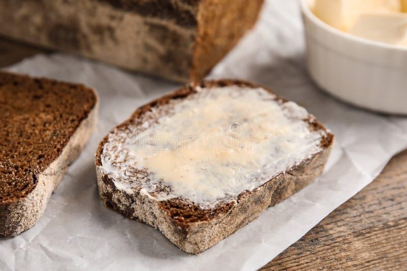 Tranche de pain de seigle avec du beurre sur la table en bois images libres de droits