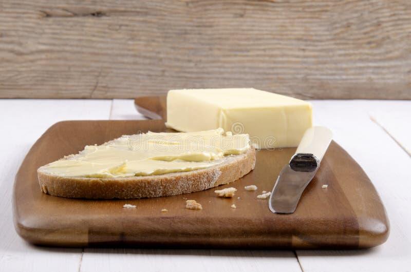 Tranche de pain sur un conseil en bois avec du beurre image stock